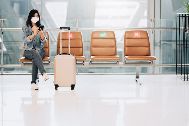 Asian woman traveler wearing face mask sitting on social distancing chair with luggage using smartphone during coronavirus or covid-19 outbreak