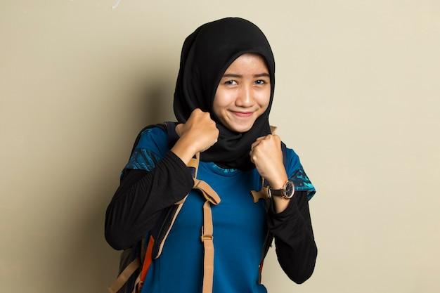Азиатская женщина-путешественница в хиджабе счастлива и взволнована, празднуя победу, выражая большой успех
