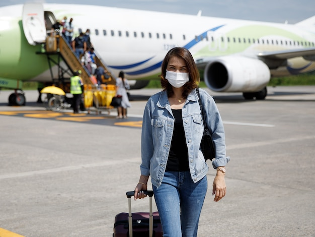 Asian woman traveler wearing protective hygiene mask holding bag walking in airport runway. idea for a journey of new normal tourist in coronavirus pandemic.