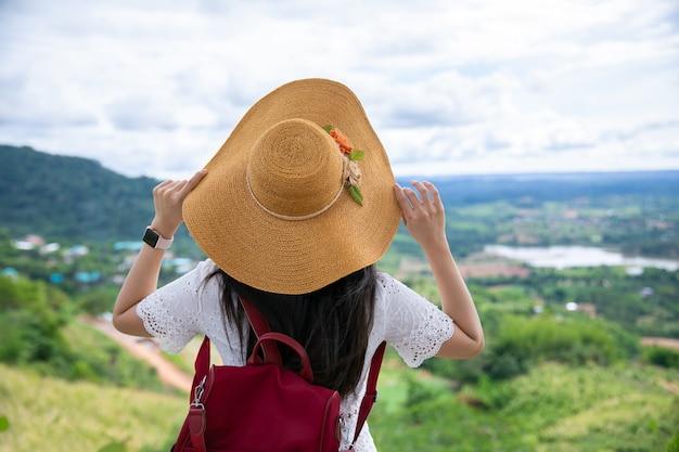 帽子を保持し、山や森を見ているバックパックを持つアジアの女性旅行者