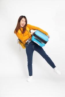 白で隔離のスーツケースを立って保持しているバックパックを持つアジアの女性旅行者。