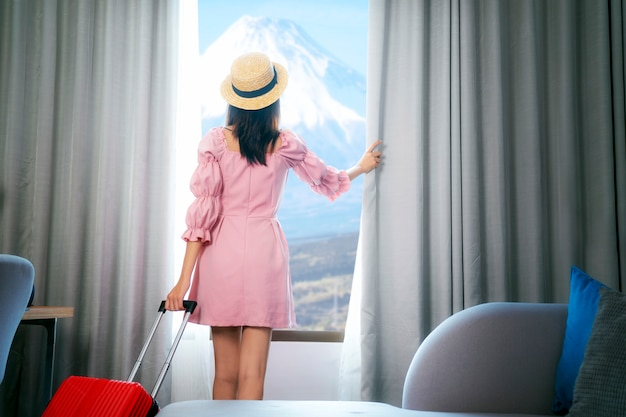 아시아 여성 여행자가 호텔 객실에 도착하고 커튼을 열고 후지 전망을 즐기십시오.