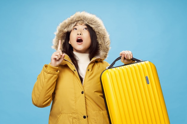 Asian woman travels with a suitcase in her hands, vacation, studio