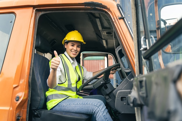 Asian woman truck driver sitting in truck cabin looking at camera.