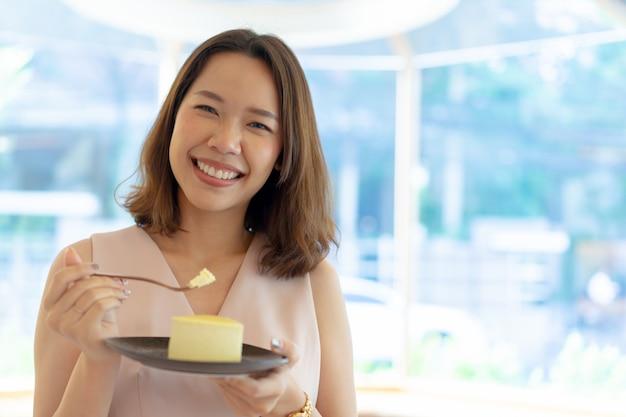 아시아 여자는 일을 듣고 휴식 시간에 카페 바에서 초콜릿 케이크의 슬라이스를 먹고하려고