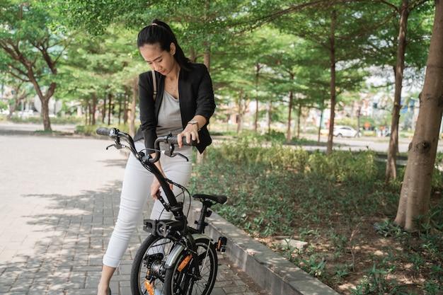 Asian woman trying fold her folding bike
