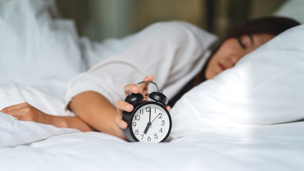 An asian woman turning off an alarm clock while sleeping on a white cozy bed in the morning