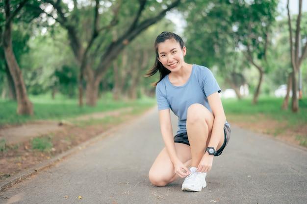 公園で走りに行く前に靴ひもを結ぶアジアの女性。