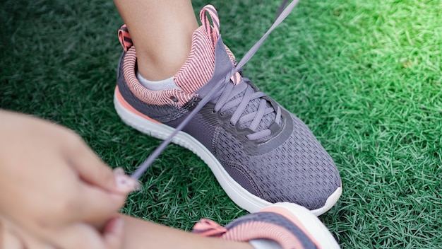 走る前にスニーカーを結ぶアジアの女性。足を閉じる