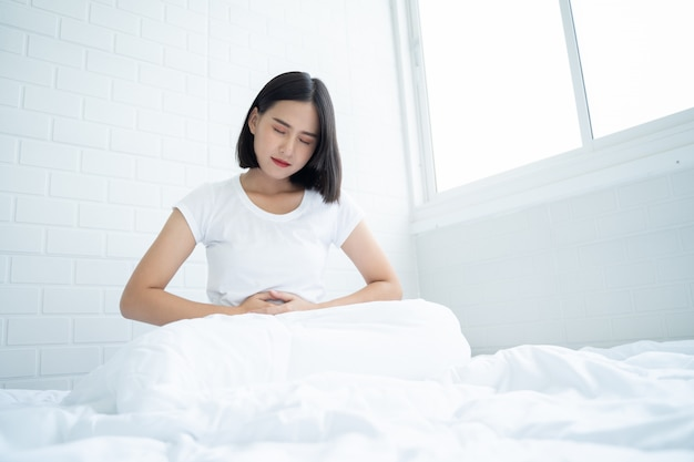 Asian woman unhappy lying on the bed looking sick, suffers from stomach ache in the bedroom