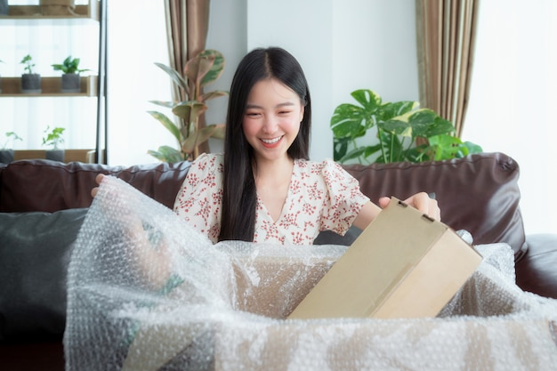 Asian woman unpack packaging after online shopping from discount store