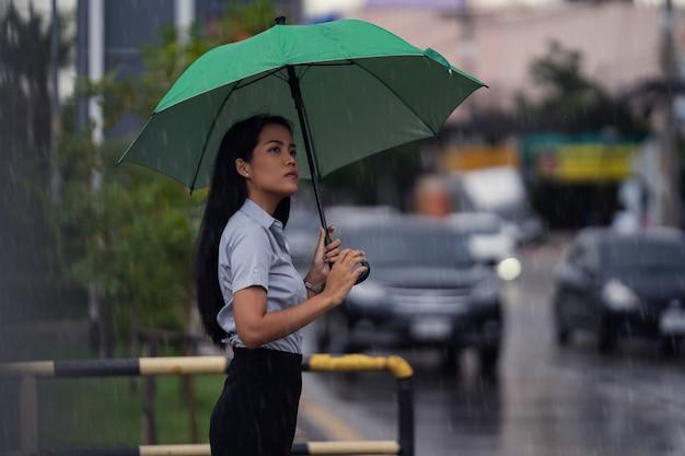 アジアの女性は雨が降っている間傘を使い、通りを歩いています。