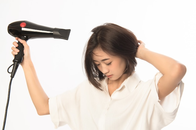 Asian woman uses hair dryer on white
