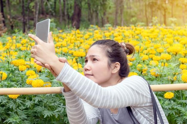 메리 골드 필드와 셀카에 스마트 폰을 사용하는 아시아 여자.