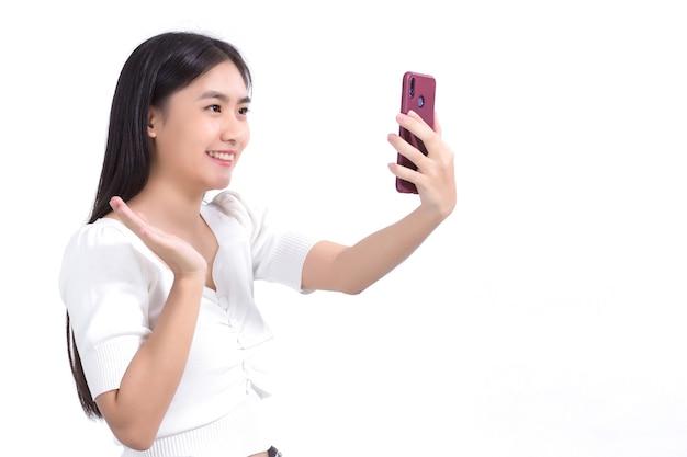白い背景の上の友人と楽しく話すためにビデオ通話にスマートフォンを使用しているアジアの女性