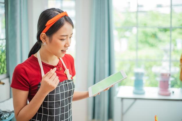Азиатская женщина с помощью планшетного компьютера готовить на кухне