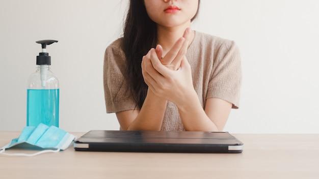 Азиатская женщина используя руки мытья дезинфицирующее средство геля спирта перед открытой таблеткой для защищает коронавирус. женщина пьет алкоголь, чтобы убрать для гигиены, когда социальное дистанцирование остается дома и сам карантин времени
