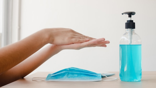 코로나 바이러스를 보호하기 위해 마스크를 착용하기 전에 알코올 젤 손 소독제 세척 손을 사용하여 아시아 여자. 사회적 거리가 집에 머무르고 자기 격리 시간에 위생을 위해 청소하기 위해 여성 푸시 알코올.