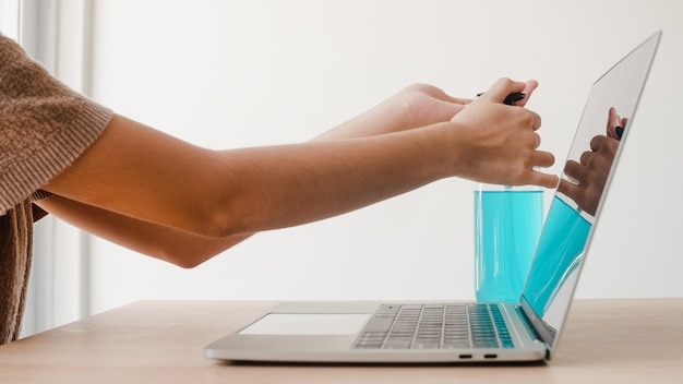 코로나 바이러스를 보호하기 위해 노트북에서 작업하기 전에 알코올 젤 소독제 세척 손을 사용하여 아시아 여자. 사회적 거리가 집에 머무르고 자기 격리 시간에 위생을 위해 청소하기 위해 여성 푸시 알코올.