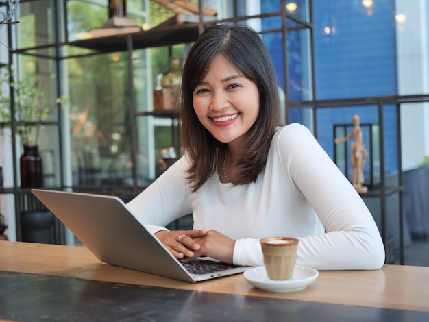Asian woman using computer laptop in coffee shop cafe