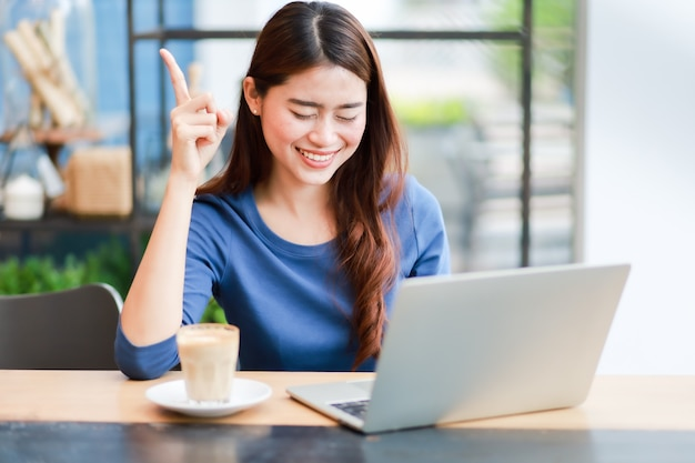 Asian woman using computer laptop and drink coffee work from home concept