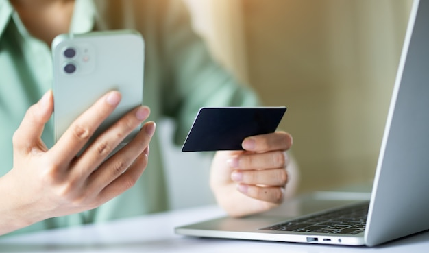 Asian woman using credit card to pay online