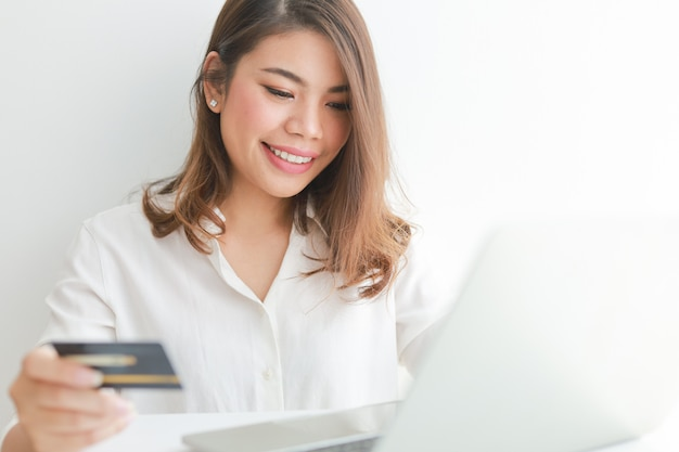 Asian woman using credit card shopping online with laptop computer,