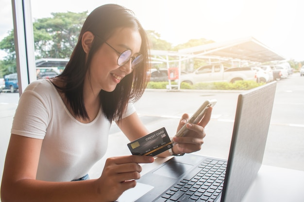 Asian woman using credit card shopping online