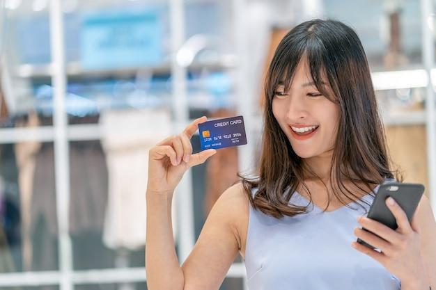 デパートでのオンラインショッピングに携帯電話でクレジットカードを使用しているアジアの女性