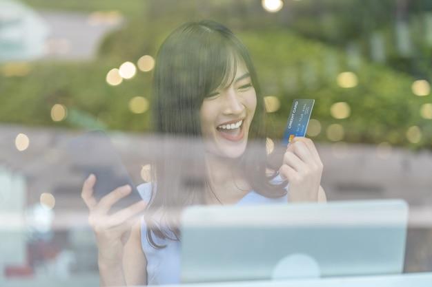 Азиатская женщина с помощью кредитной карты с мобильным телефоном для покупок в интернете в современном кофе