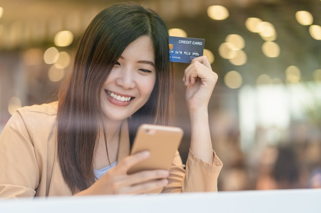Asian woman using credit card with mobile phone for online shopping in department store
