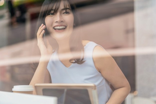 Asian woman using credit card with mobile phone for online shopping in modern coffee shop