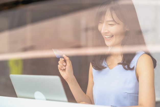 Asian woman using credit card with mobile phone and technology laptop for online shopping