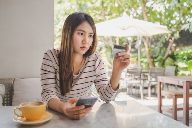 Asian woman using credit or debit card by application on smartphone for payment online