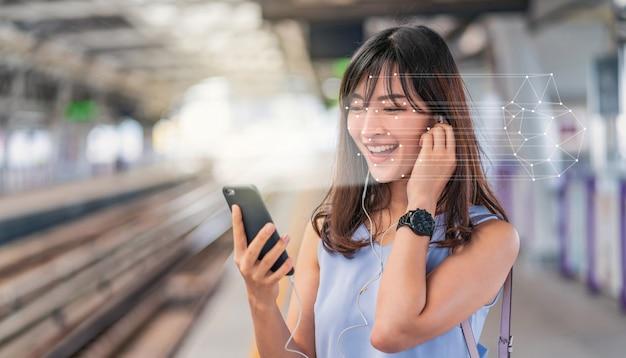 철도에서 스마트 휴대폰을 통해 얼굴 인식을 사용하고 음악을 듣는 아시아 여성