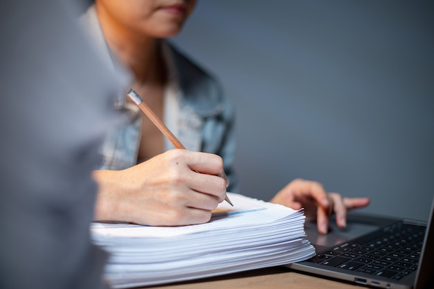 Asian woman using finger for touch on computer notebook to search information and data.chinese manager take notes with pencil on the paper.study and education with online internet.