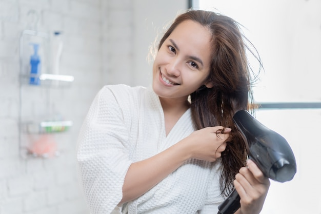Asian woman using hair dryer after shower in the bathroom