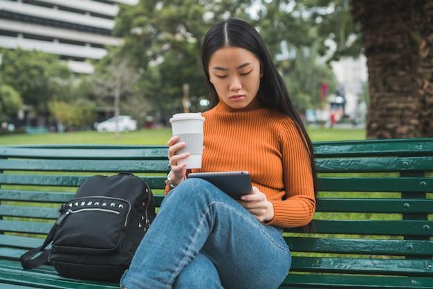 Азиатская женщина, используя ее цифровой планшет
