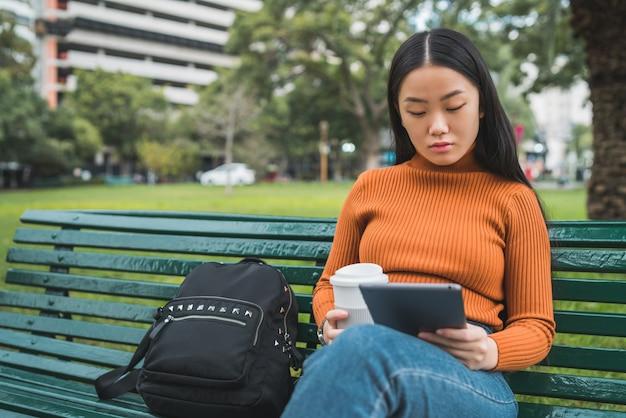 Азиатская женщина, используя ее цифровой планшет.