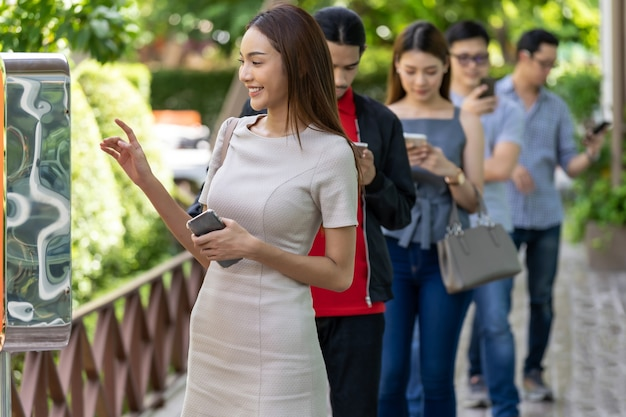 Asian woman using kiosk of food ordering with social distance queue in line before getting in fast food restaurant. online technology self service new normal restaurant concept.