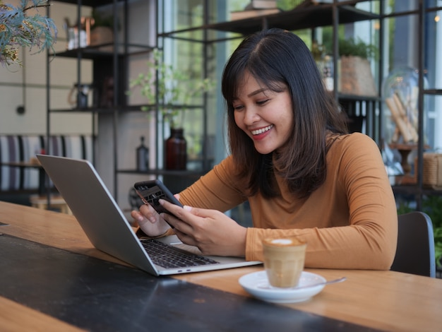 Asian woman using laptop in coffee shop cafe