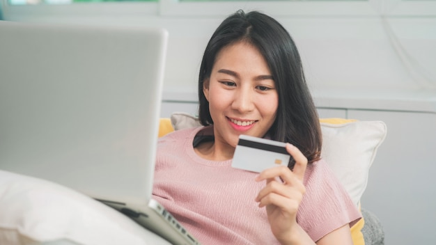 Asian woman using laptop and credit card shopping ecommerce, female relax feeling happy online shopping sitting on sofa in living room at home. lifestyle women relax at home concept.