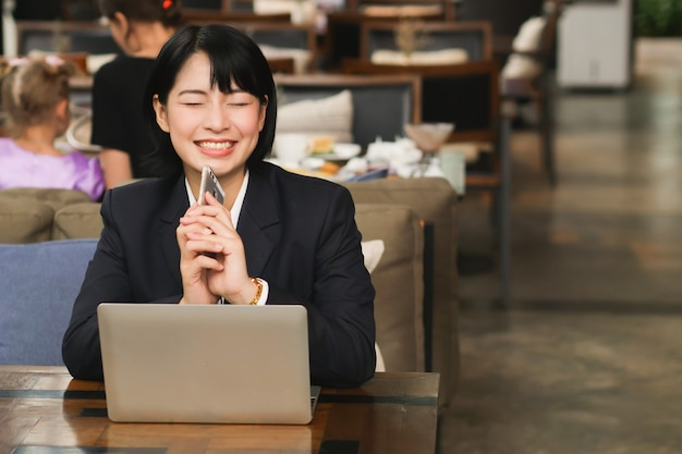 Asian woman using laptop and  drinking coffee  in coffee shop cafe