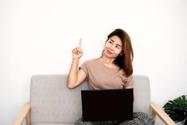 上向きのソファの手に座ってラップトップを使用してアジアの女性
