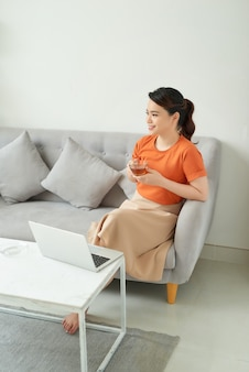 Asian woman using a laptop while having a tea in her living room