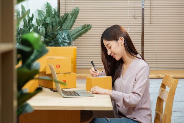 オンラインマーケティング中小企業の所有者の在宅勤務のパッケージボックスにノートパソコンの書き込みを使用してアジアの女性