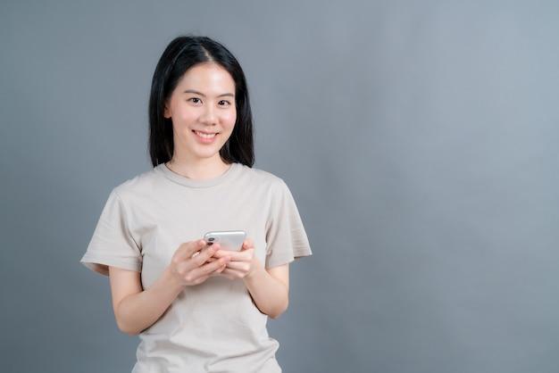 携帯電話のアプリケーションを使用して、ソーシャルネットワークで遠く離れたオンライン通信を楽しんだり、灰色の背景で隔離の買い物を楽しんでいるアジアの女性