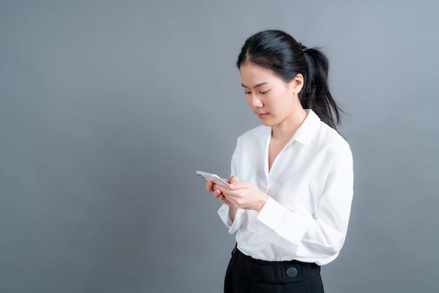 Азиатская женщина, использующая приложения для мобильных телефонов, наслаждается дистанционным онлайн-общением в социальной сети или покупками, изолированными на сером фоне