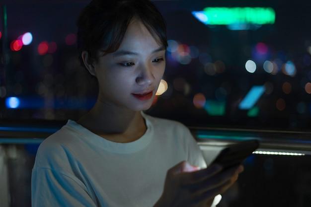 夜に携帯電話を使用してアジアの女性