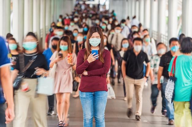 흐릿한 인식할 수 없는 비즈니스 사람들 사이에서 휴대전화를 사용하는 아시아 여성